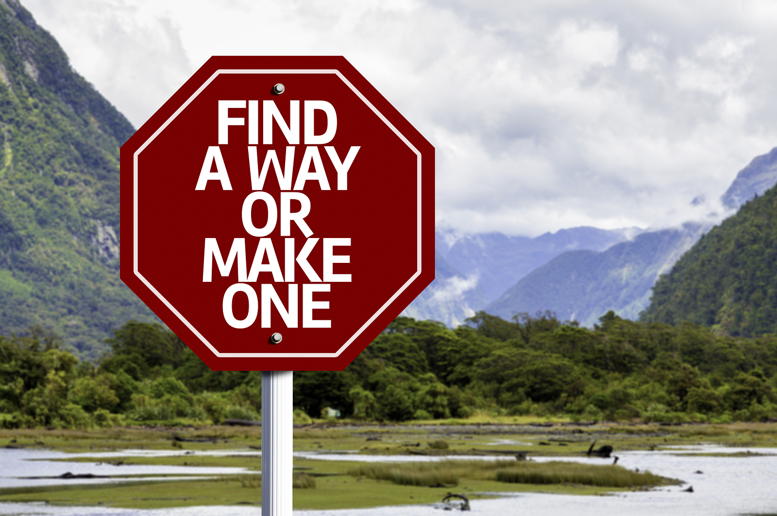 Find A Way Or Make One written on red road sign with landscape b